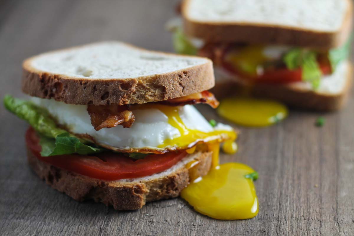 Vertical close up of two low FODMAP BLT sandwiches