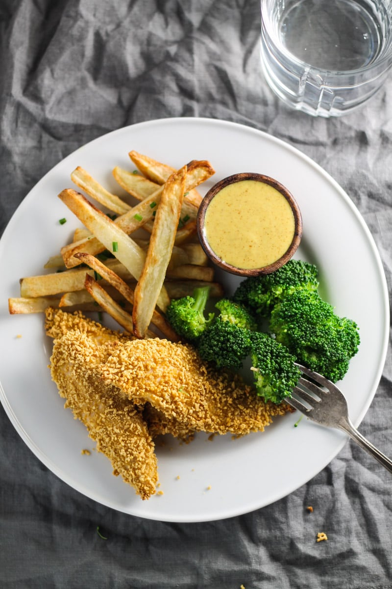 A white plated filled with three Low FODMAP Chicken Tenders, steamed broccoli, homemade fries, and a small bowl of creamy maple mustard for dipping.