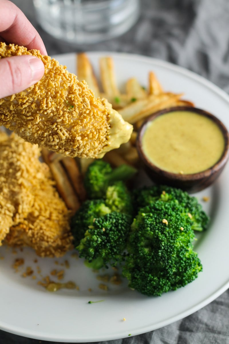 A crispy chicken tender dipped into a creamy maple mustard dipping sauce.