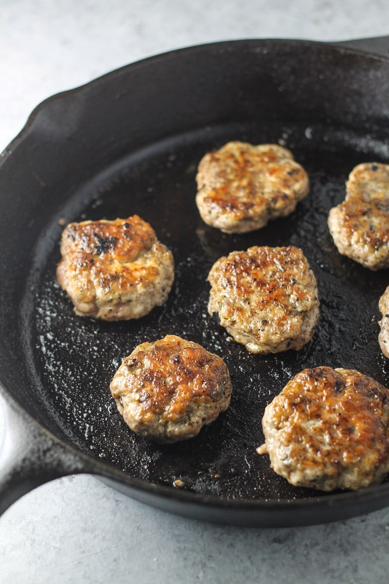 Low FODMAP breakfast sausage patties cooked in a cast-iron skillet.
