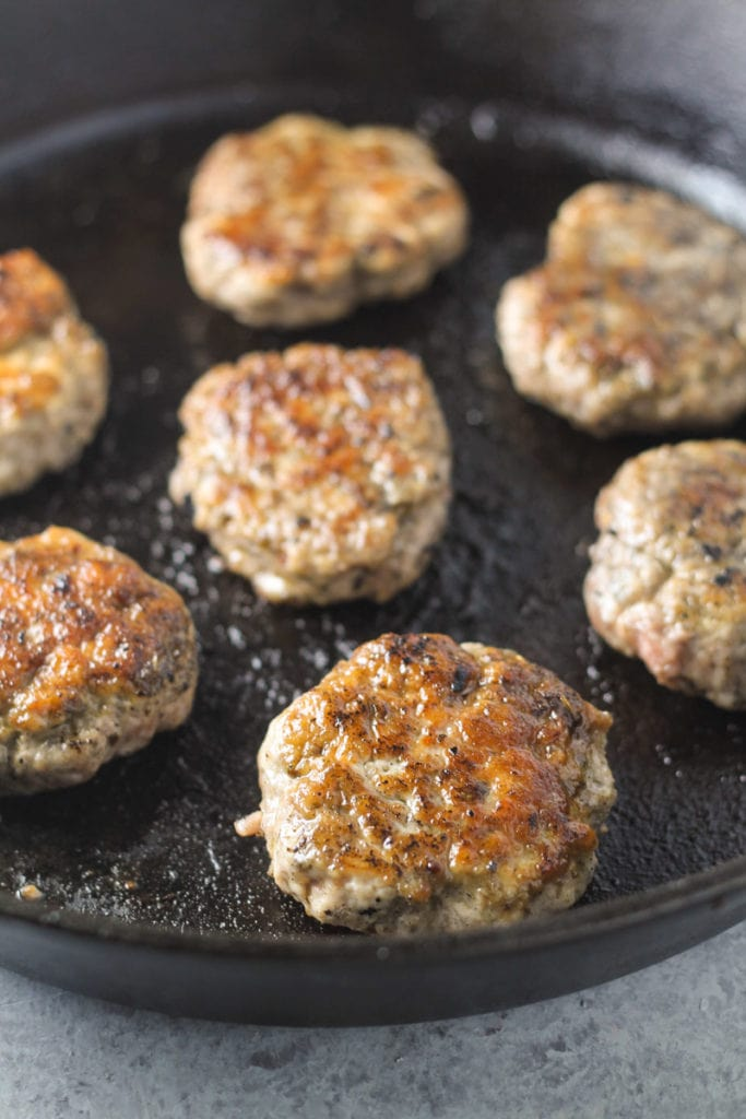 Cooked breakfast sausage patties in a cast-iron skillet