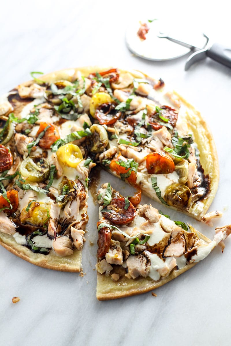 A sliced pizza topped with chicken, multi-color roasted tomatoes, fresh basil, mozzarella, and balsamic.