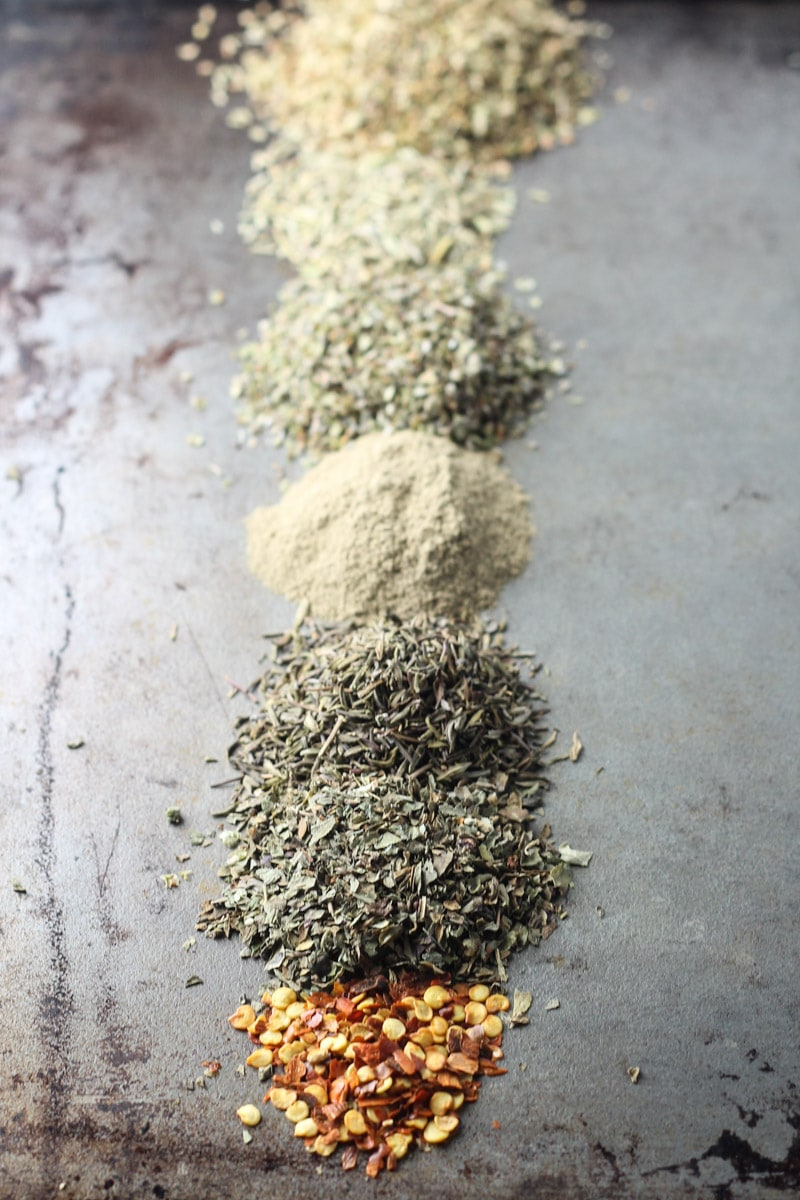 Separate piles of spices in Italian seasoning on sheet pan