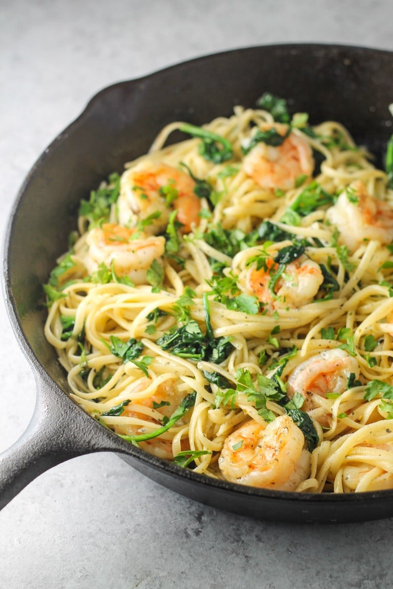 Cooked linguini, wilted spinach, and shrimp topped with fresh parsley in a cast iron skillet