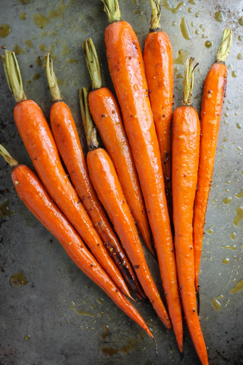 Roasted green top carrots on sheet pan.