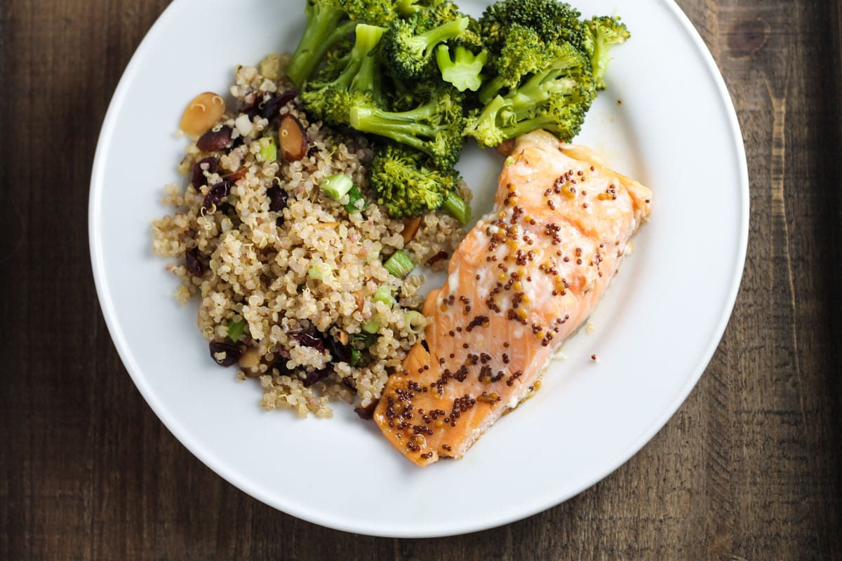 A plate of salmon with quinoa pilaf and roasted broccoli
