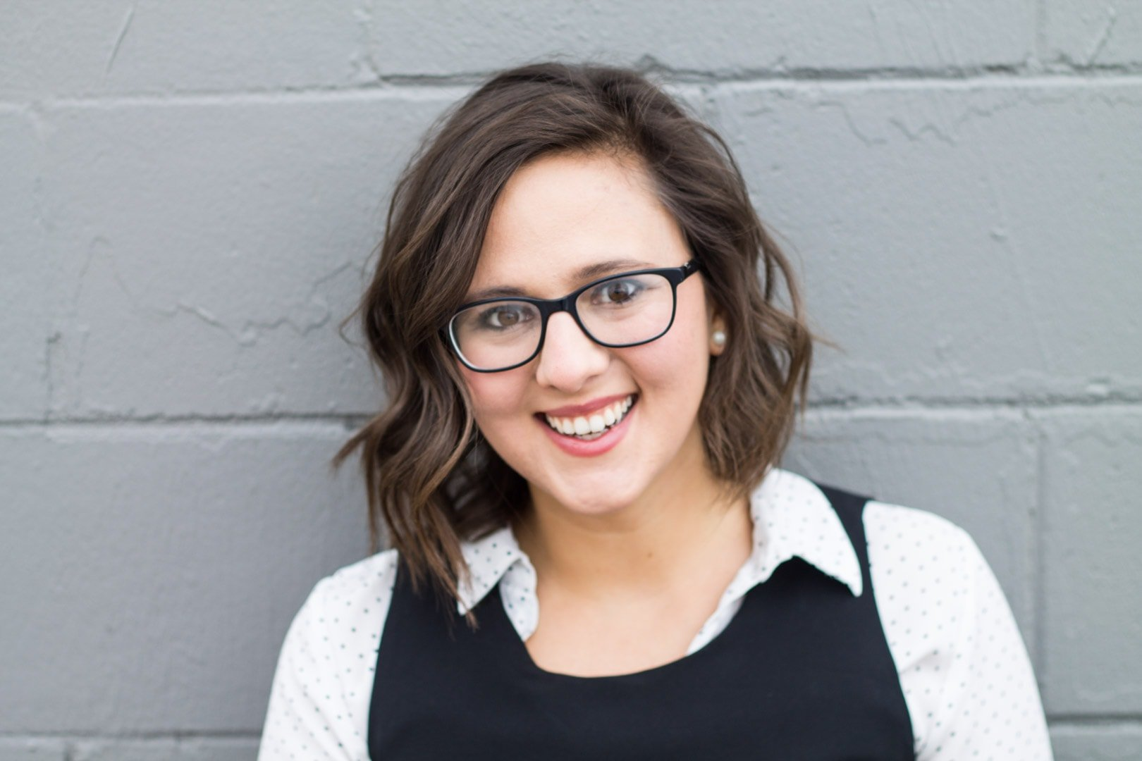 Hey, I'm Em! (Em Schwartz RDN) This is a picture of my smiling. I have wavy dark brown shoulder-length hair and wear black thick-framed glasses.
