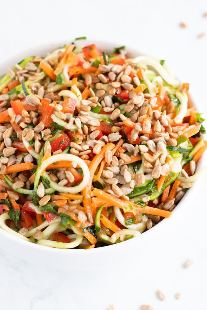 A close up of a white bowl filled with low FODMAP Asian Zoodle Salad: zucchini noodles, carrot shreds, diced red pepper, chives, cilantro and sunflower seeds tossed with an Asian-inspired vinaigrette.