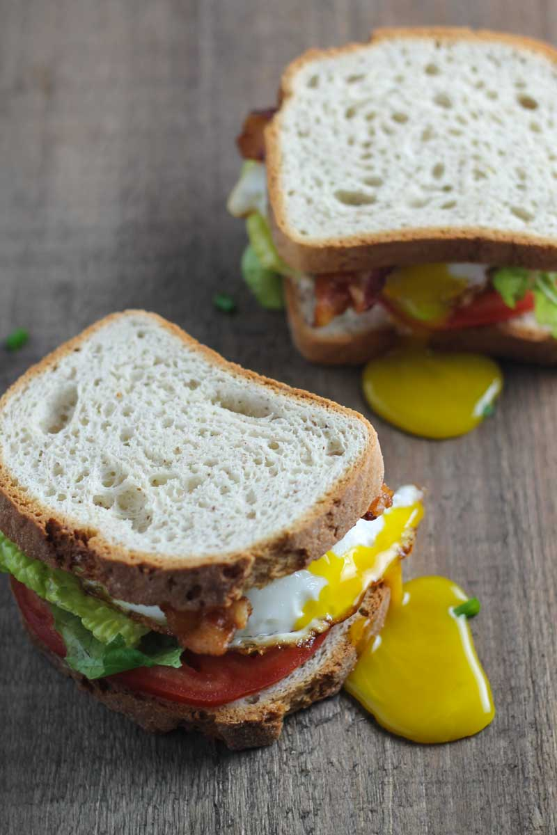 Two low FODMAP BLT sandwiches made with a drippy fried egg.