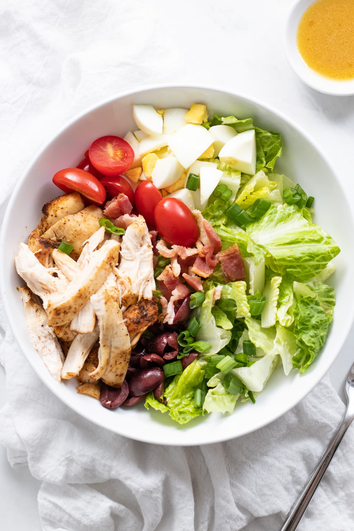 A shallow bowl filled with lettuce, chicken, bacon crumbles, diced hard-boiled egg, cherry tomatoes, and kalamata olives.