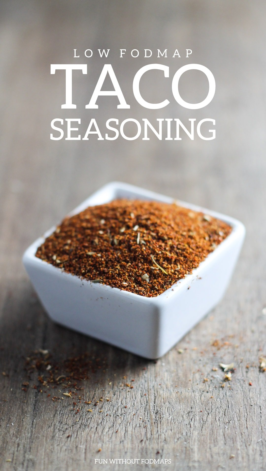 Low FODMAP Taco Seasoning in a small white dish on a wood surface