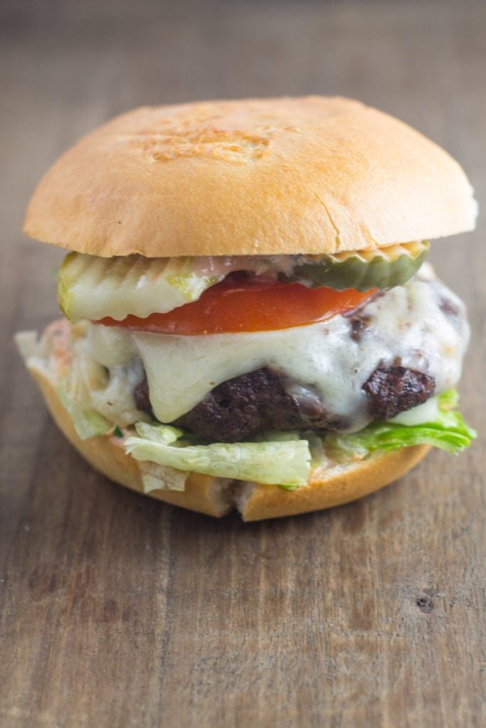 A low FODMAP California Burger filled with hamburger, Swiss cheese, lettuce, tomato, and pickle.