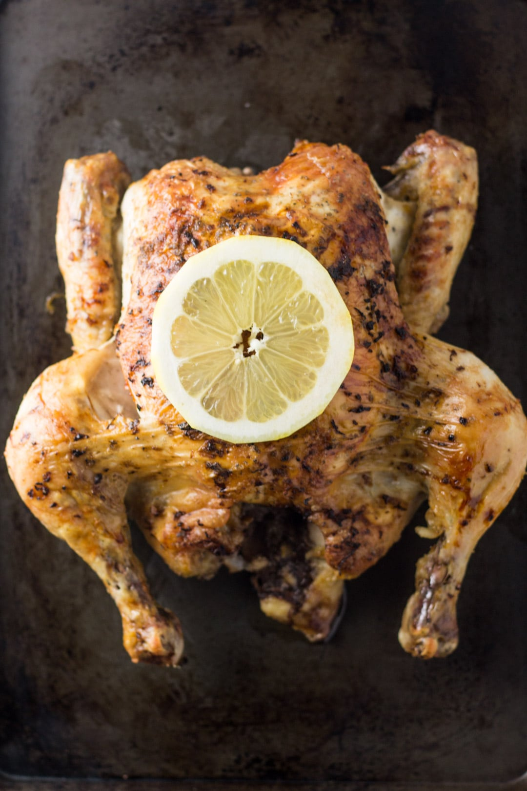 Looking down at a lemon roasted whole chicken topped with a lemon slice.