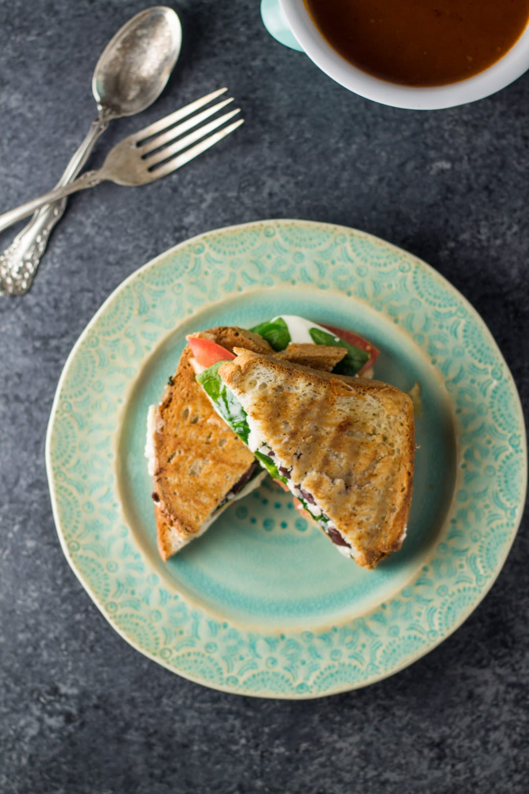 Overhead shot of low FODMAP Mediterranean grilled cheese on a blue plate.