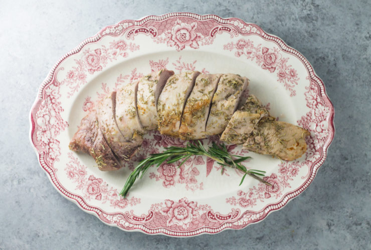 Overhead shot of low FODMAP pork tenderloin with rosemary on an antique plate