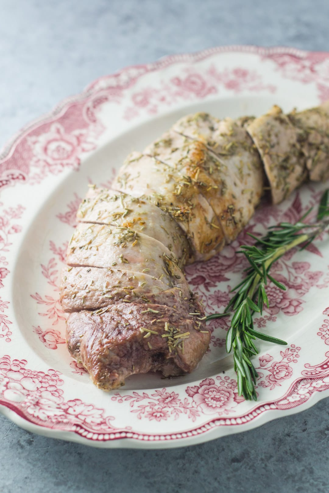 Slices of low FODMAP pork tenderloin with rosemary on an antique plate