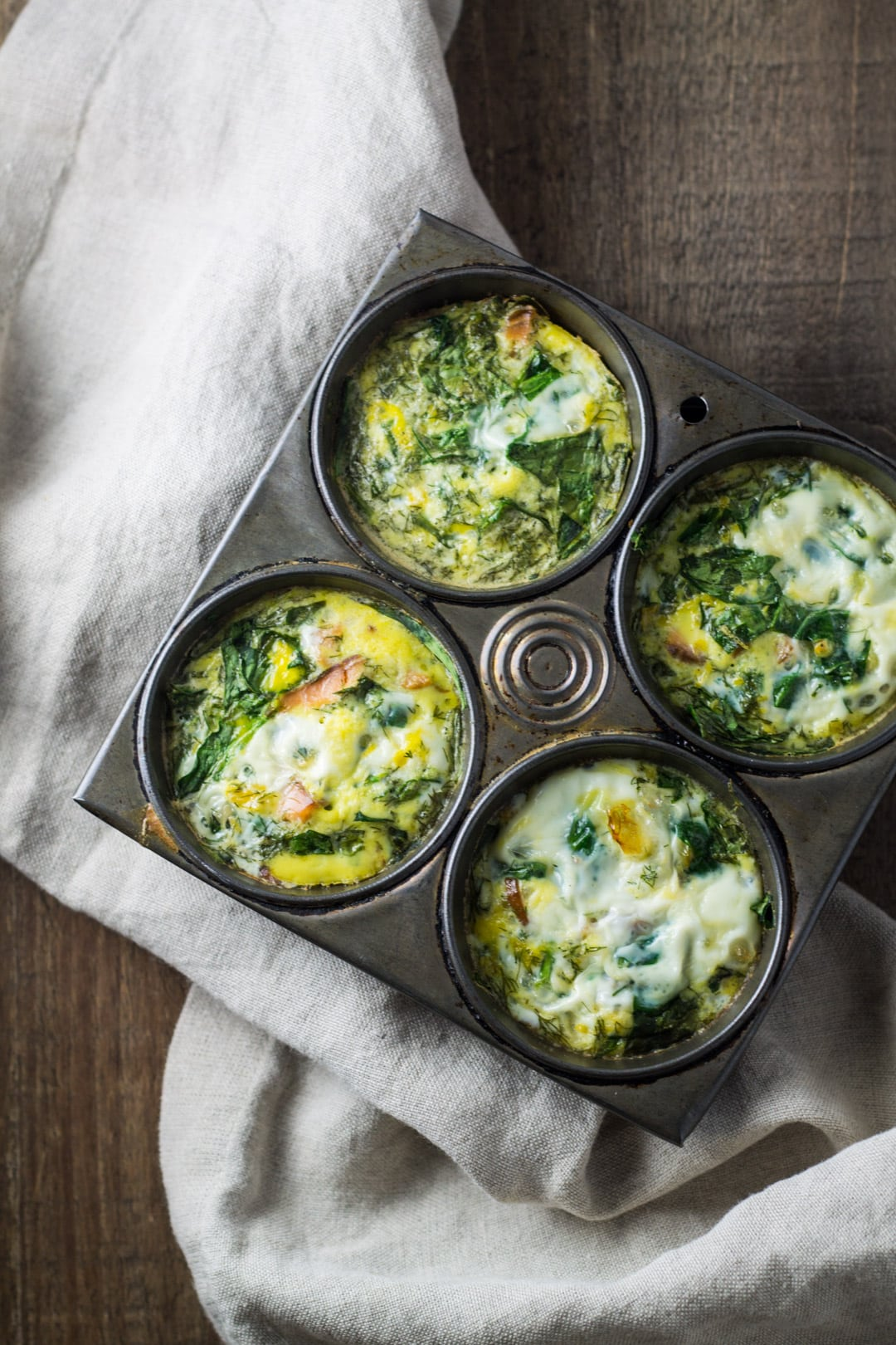 A four-cup muffin tip filled with smoked salmon and spinach egg muffins.