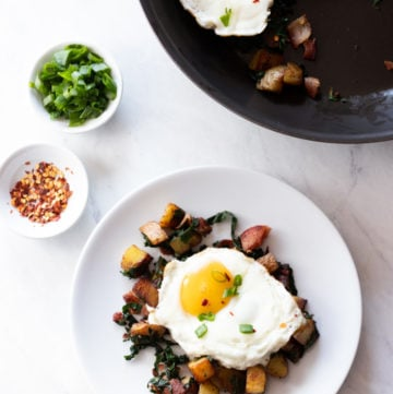 A skillet and plate containing low FODMAP Bacon, Chard, and Potato Hash sit on a white marble slab. There are also white pinch bowls filled with red pepper flakes and sliced green onion tops.