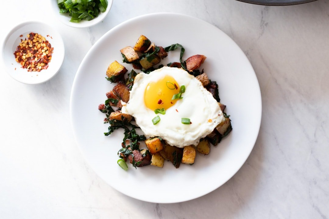 An overhead shot of a plate filled with a breakfast potato hash topped with an egg.