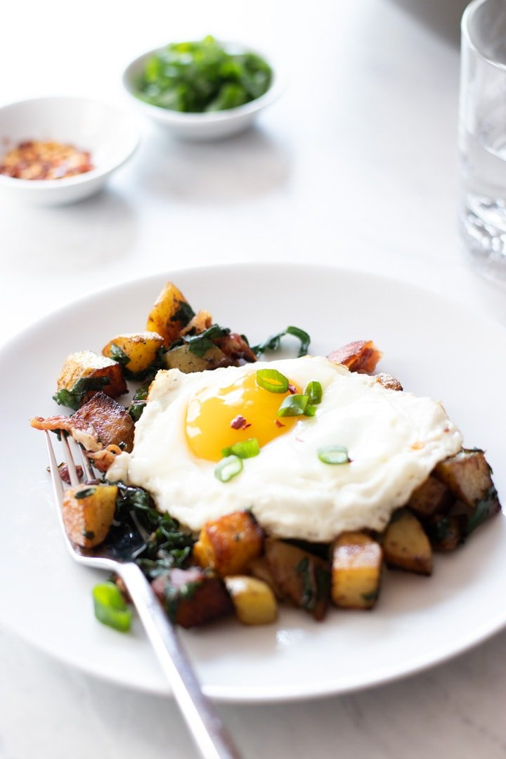 A fork rests on a plate filled with breakfast hash.
