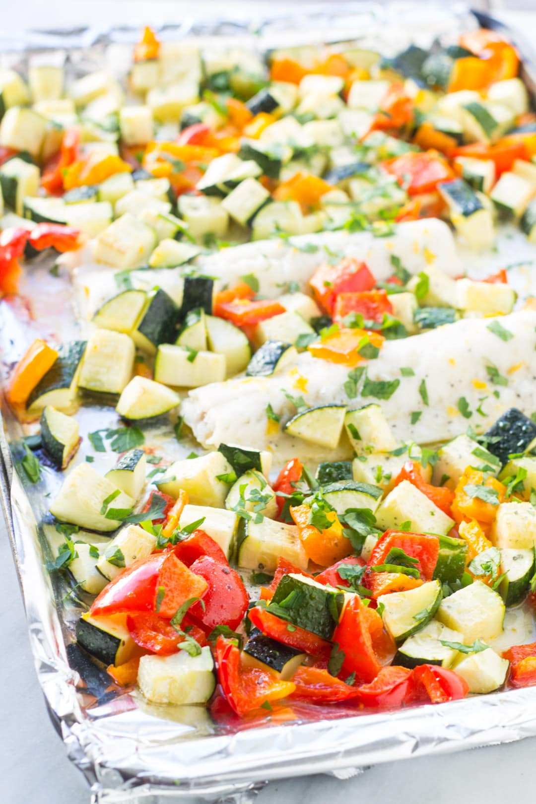 A sheet pan with baked cod, zucchini and bell peppers flavored with lemon and parsley.