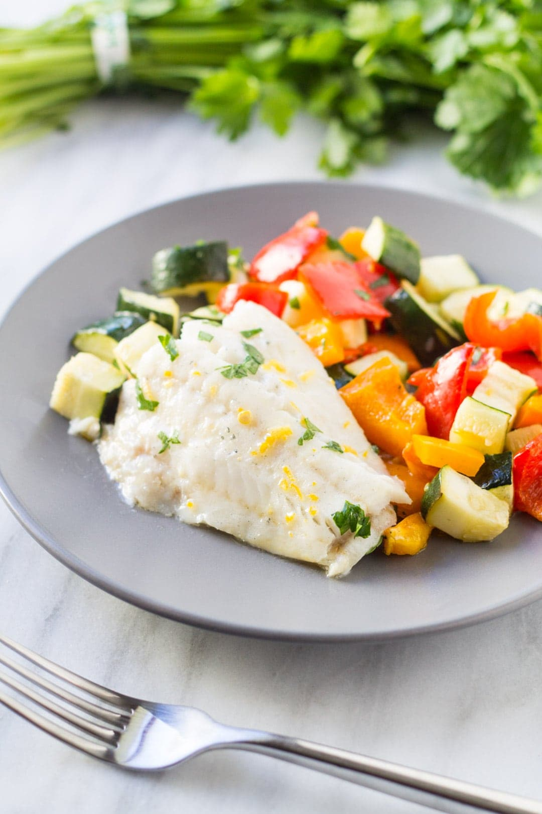 Baked lemon cod, bell peppers, and zucchini on a gray plate.