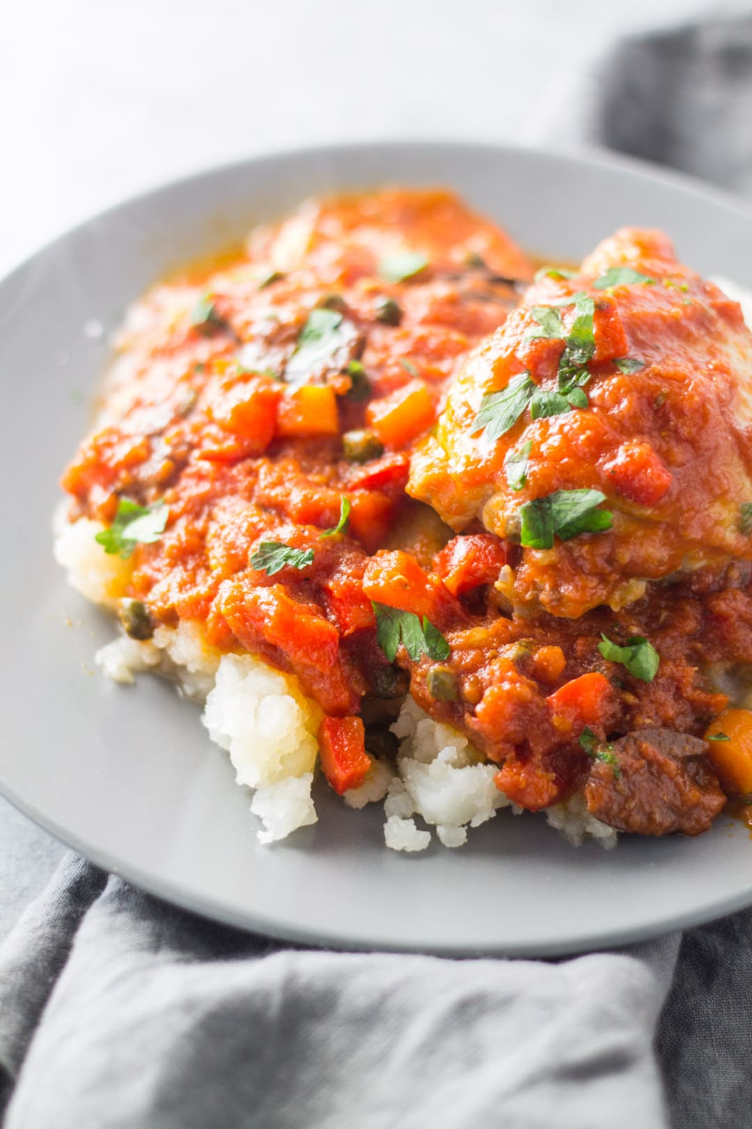 A serving of chicken cacciatore over mashed potatoes