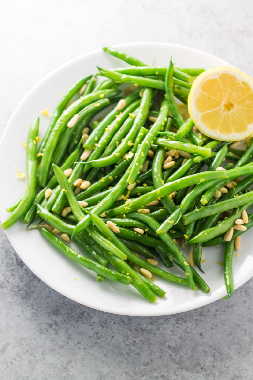 A plate filled with green beans dotted with toasted pine nuts and fresh lemon zest. A lemon half adorns the plate.