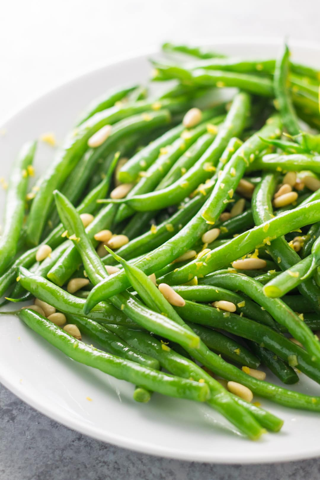 A close-up of green beans with a sprinkle of lemon zest and toasted pine nuts.
