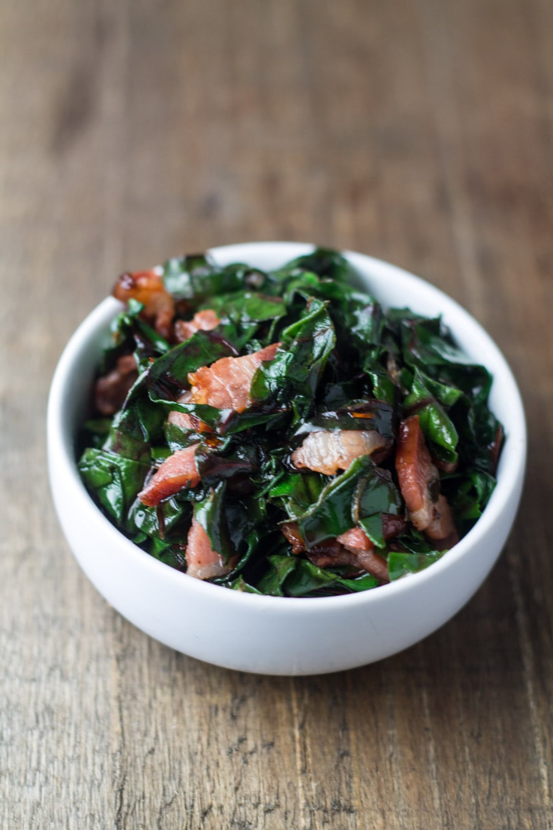 A small bowl of Swiss chard and bacon crumbles.