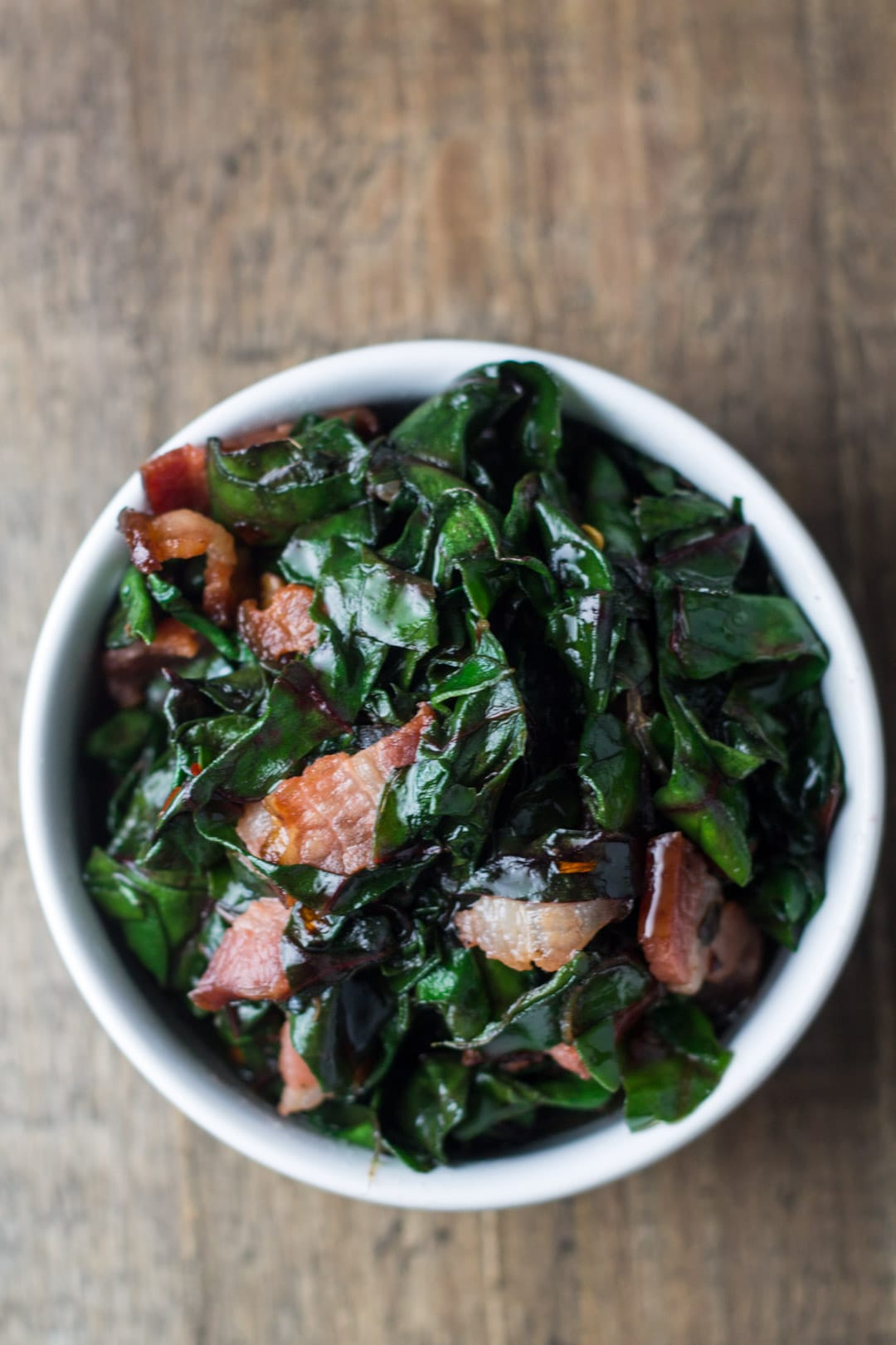 Looking down at a small bowl filled with sauteed Swiss chard with bacon