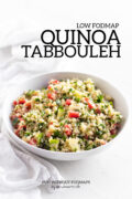 A shallow white bowl filled with a mixture of quinoa, tomato, cucumber, and fresh herbs. The bowl sits on a white marble background with a white cloth napkin on the side. A black text overlay reads Low FODMAP Quinoa Tabbouleh