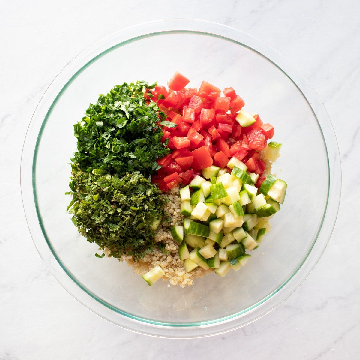 A large glass bowl with cooked quinoa, diced tomato, diced cucumber, chopped fresh mint and parsley ready for mixing