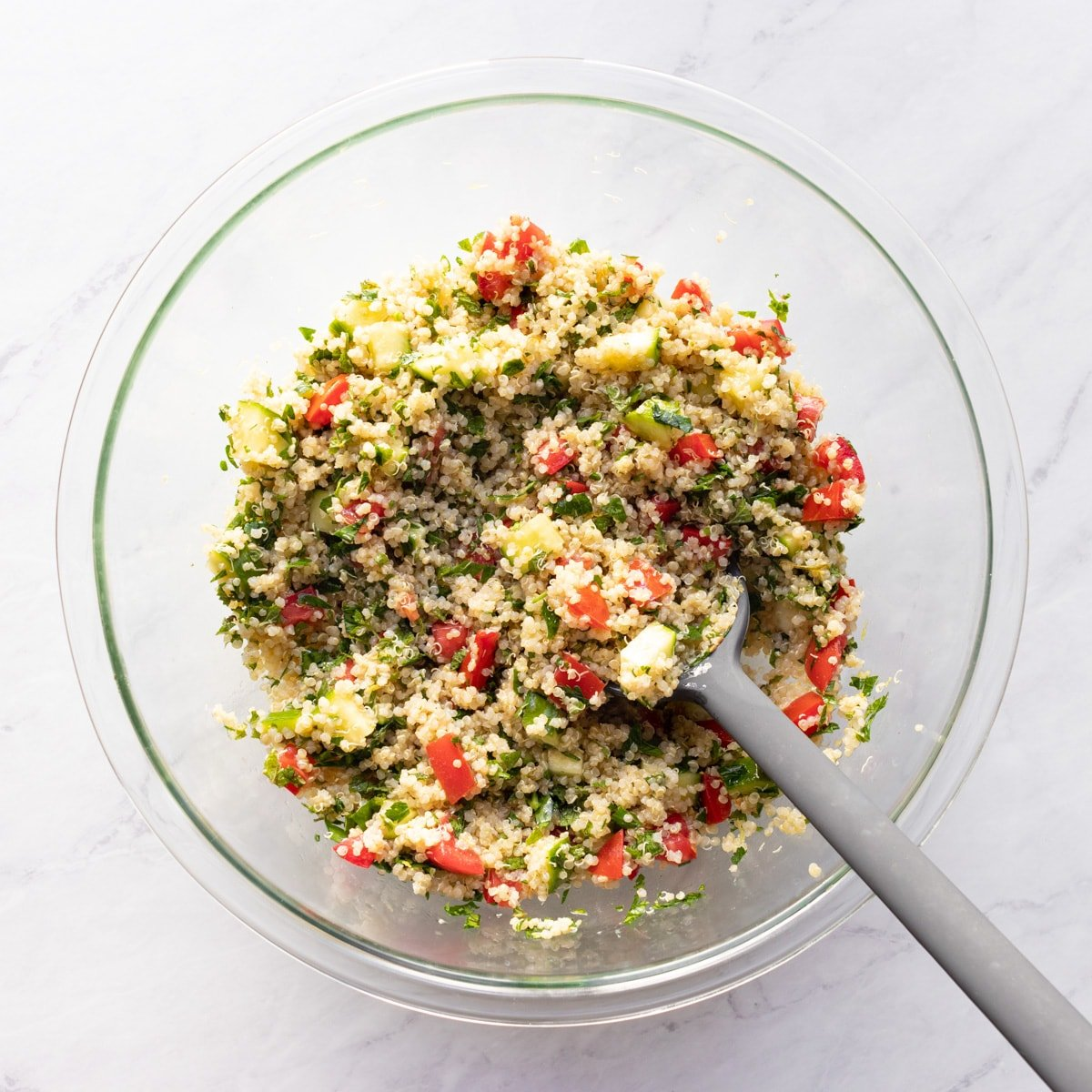 Quinoa, fresh veggies and herbs have been mixed with a lemon vinaigrette in a large glass bowl with a gray silicone scoopula