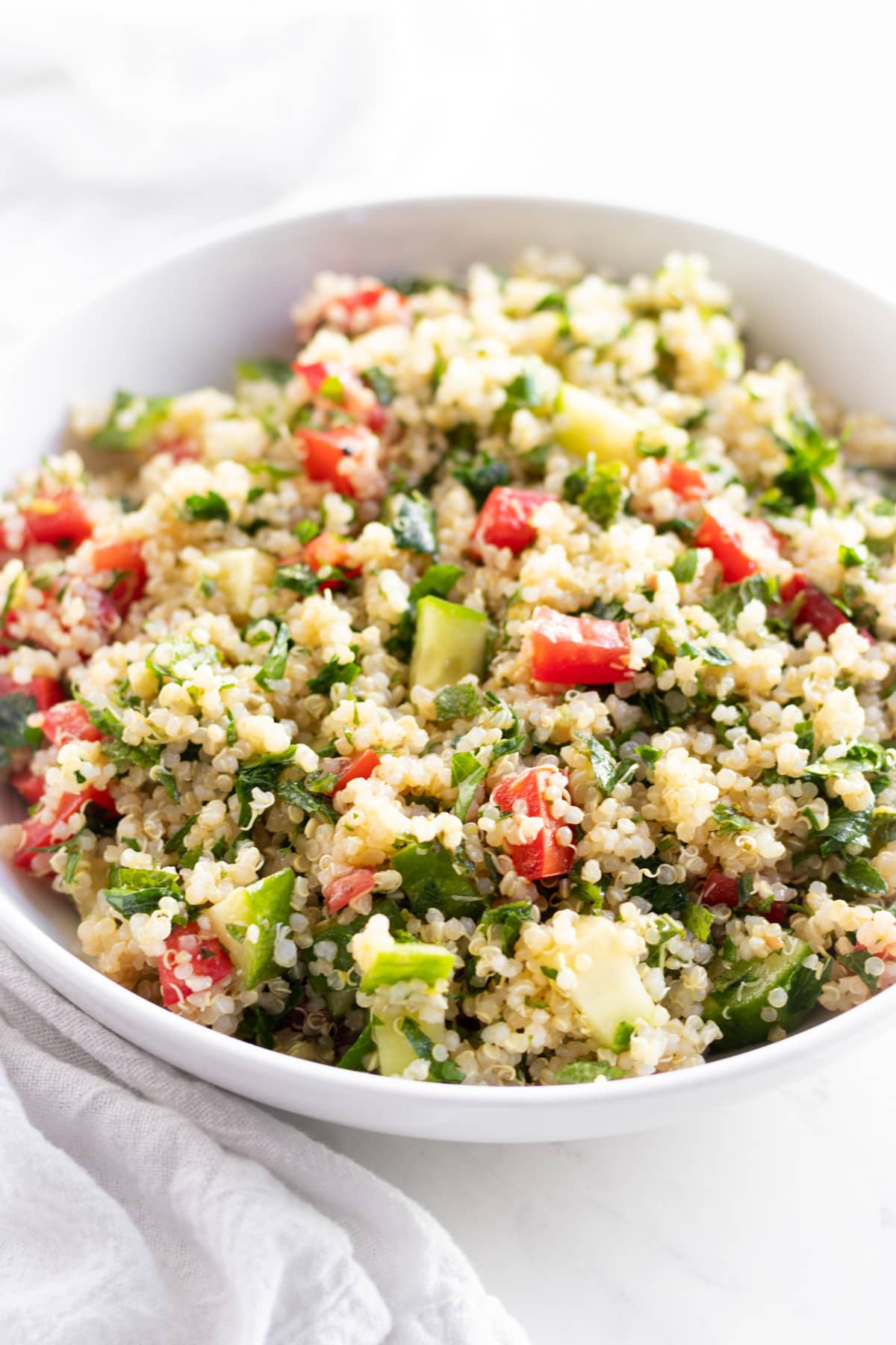 Close up of a grain salad made with quinoa, tomatoes, cucumber, and fresh herbs