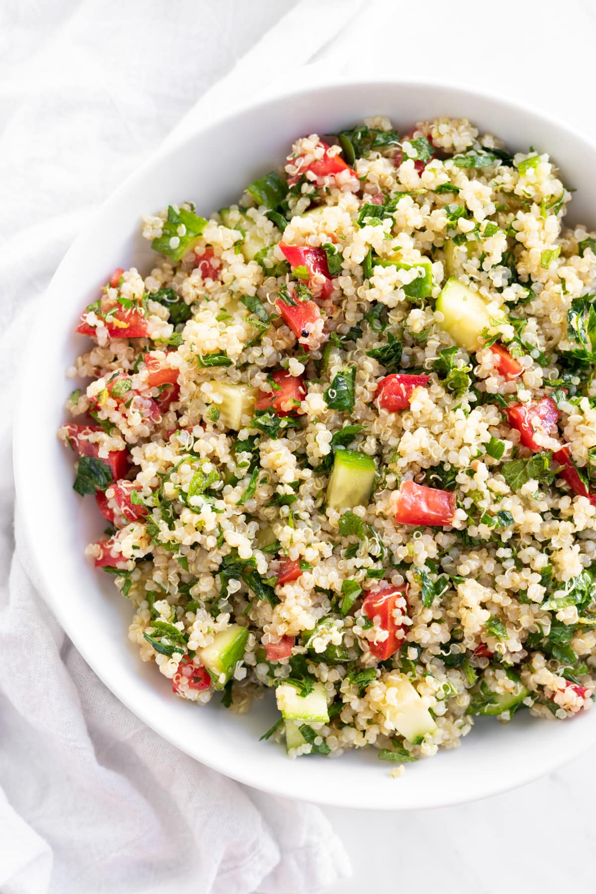 White quinoa salad studded with diced cucumber, roma tomato, and flecks of parsley and mint.