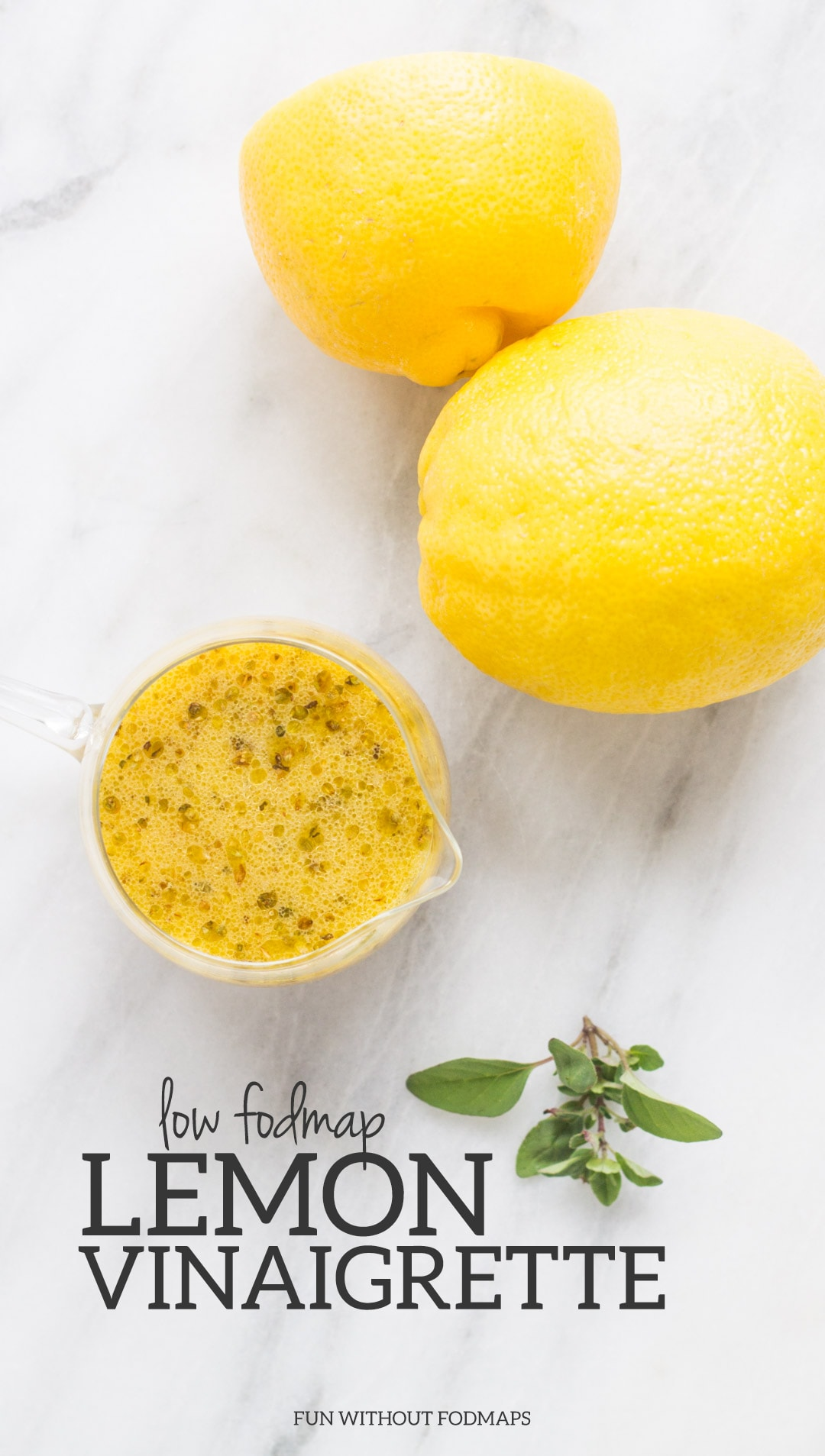 """A cup of low FODMAP lemon vinaigrette surrounded by lemons and herbs. In the white space, a black text overlay reads """"Low FODMAP Lemon Vinaigrette"""""""