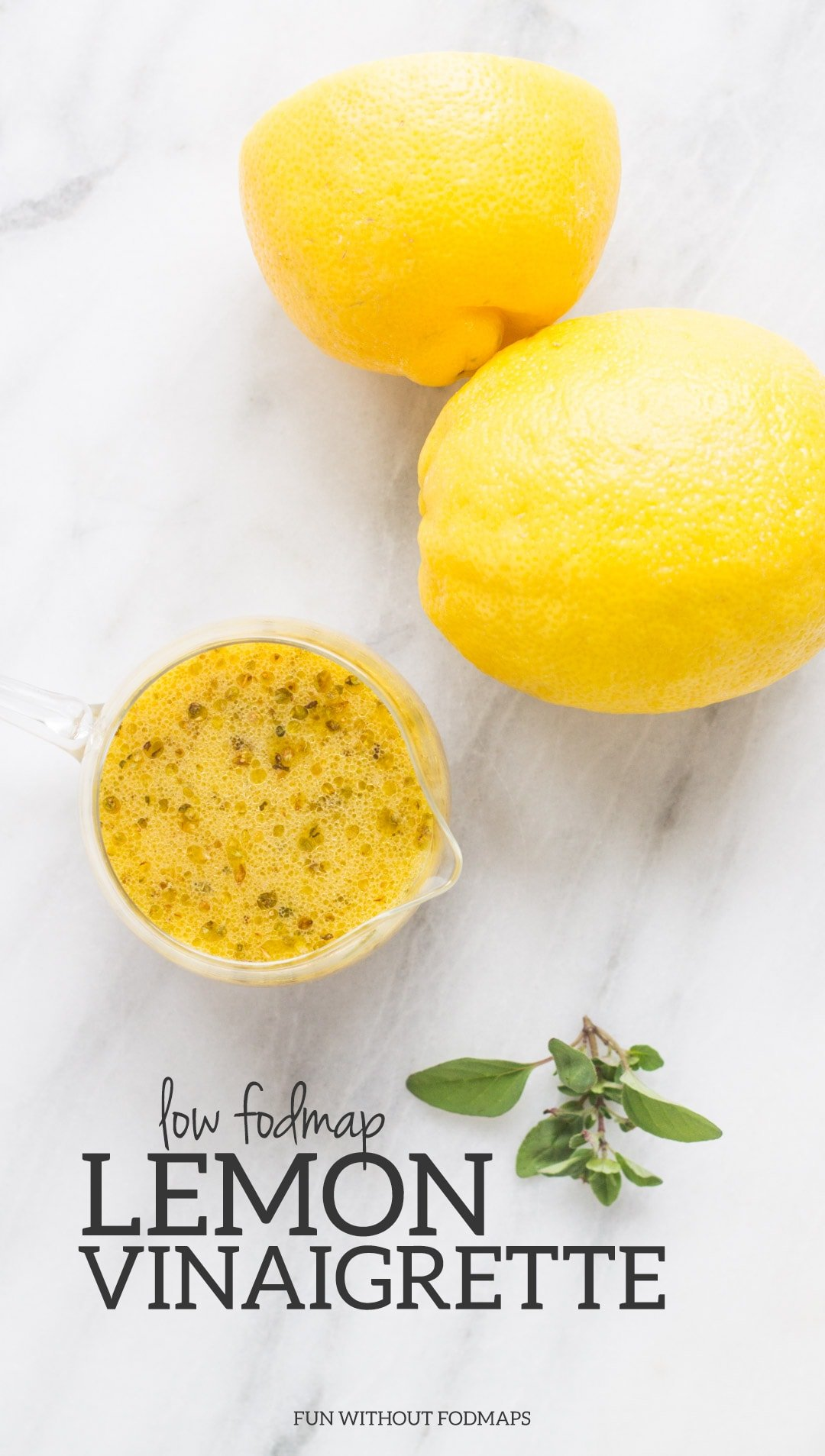 A cup of low FODMAP lemon vinaigrette surrounded by lemons and herbs