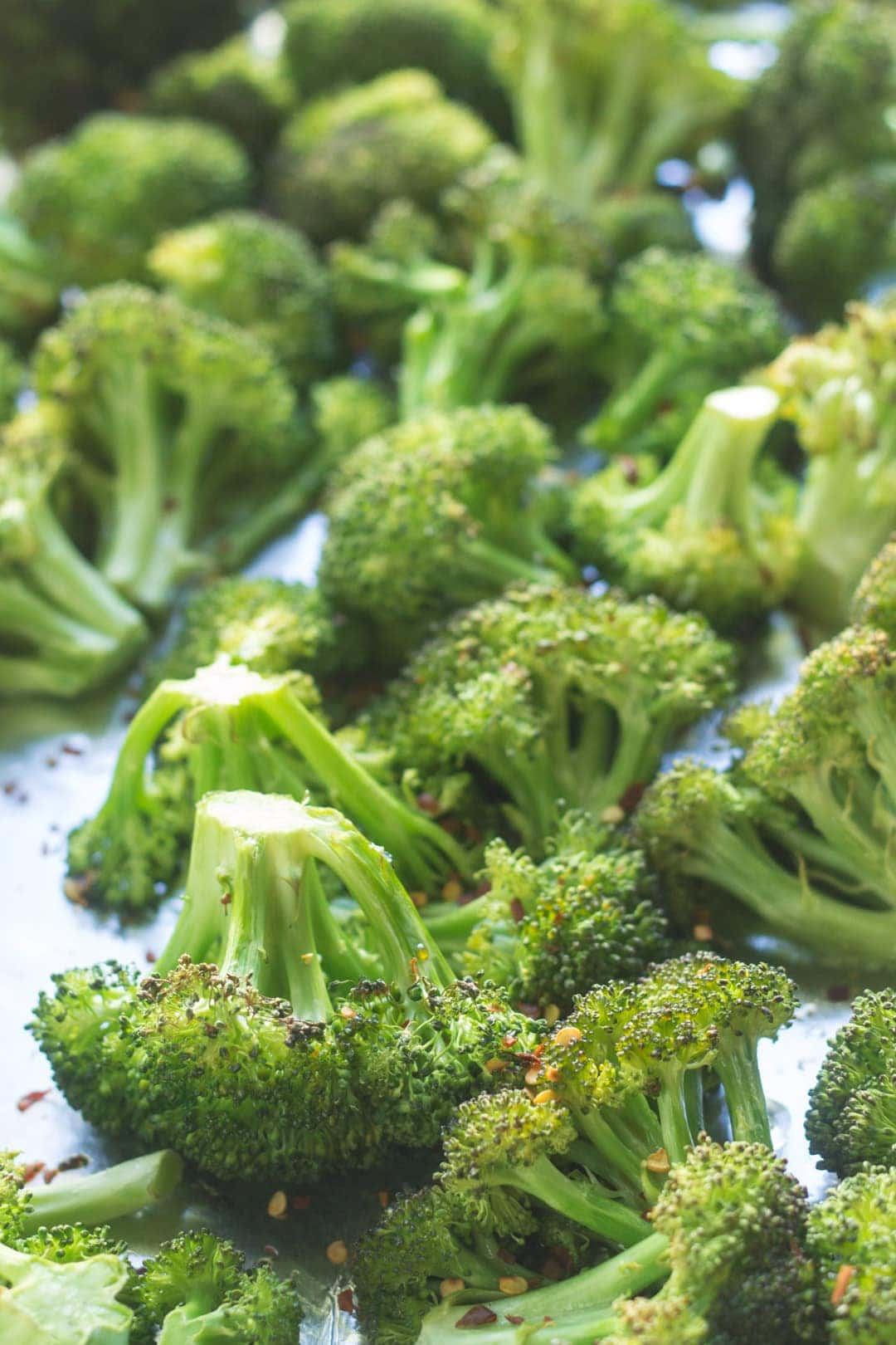 Roasted broccoli sprinkled with red pepper flakes on a sheet pan lined with aluminum foil.