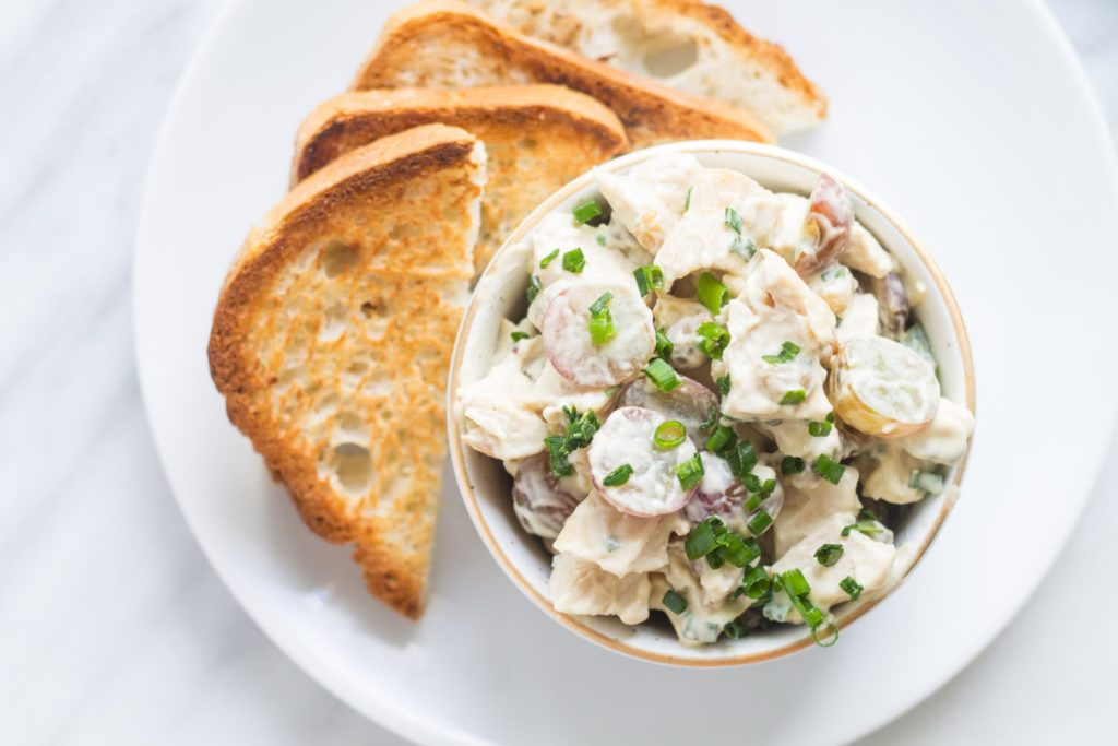 Overhead centered shot of low FODMAP chicken salad and grapes with toast