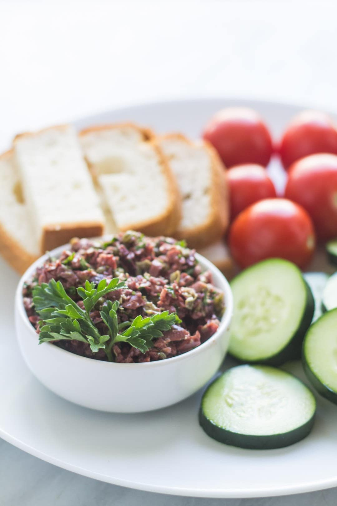 Bowl of low FODMAP olive tapenade surrounded by veggies and gluten-free bread