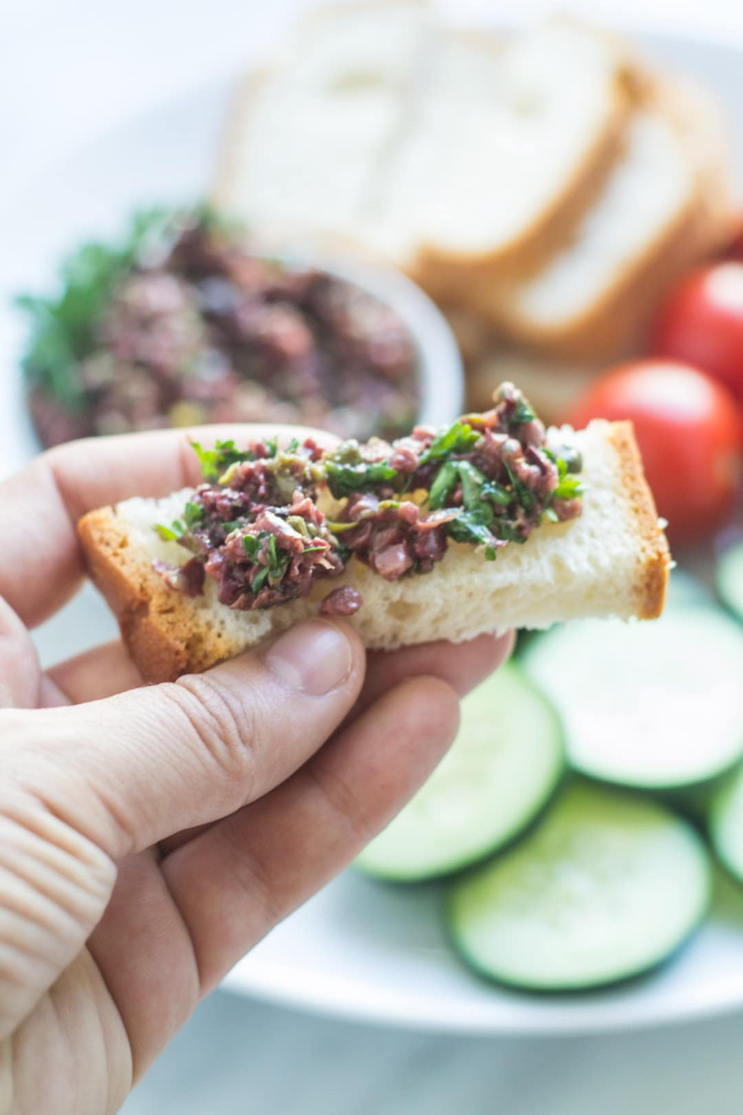 Piece of gluten-free bread topped with low FODMAP olive tapenade
