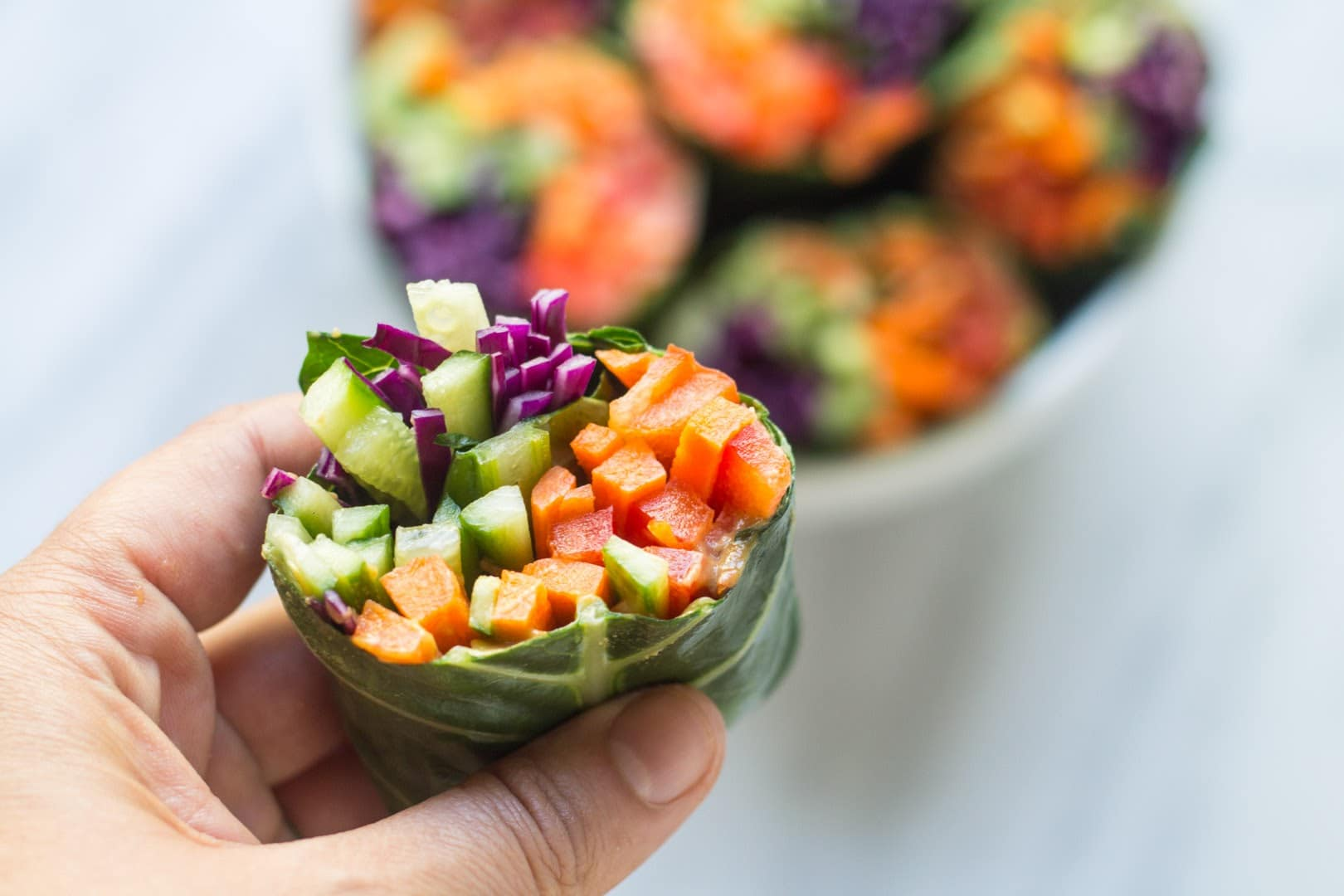 Hand holding low FODMAP rainbow wrap