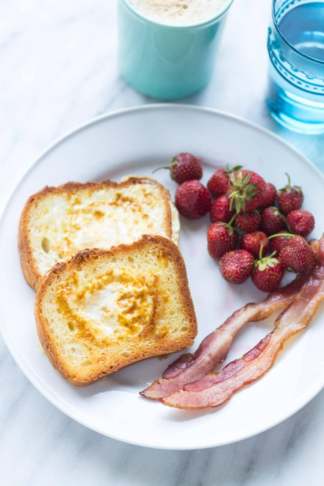 Plate of low FODMAP toad in a hole (toast with a cooked egg in the center), slices of bacon and strawberries