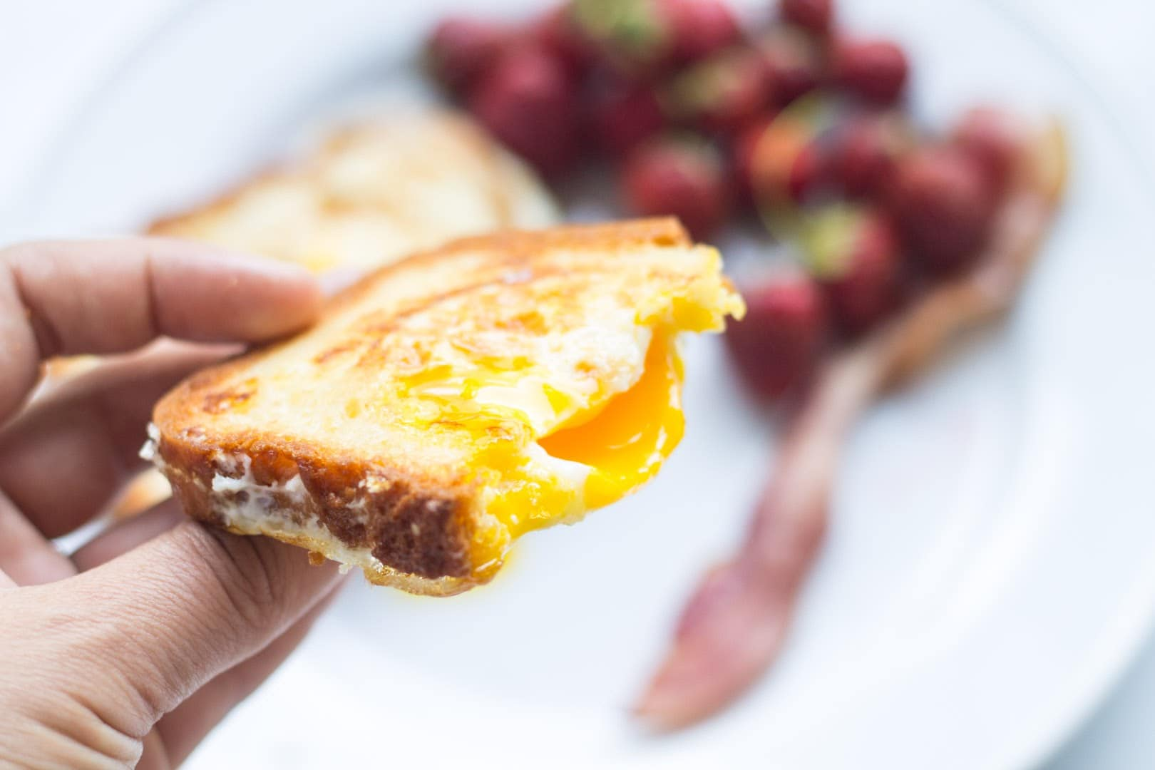 A hand holding a slice of toasted bread containing an over-medium egg cooked into the center.