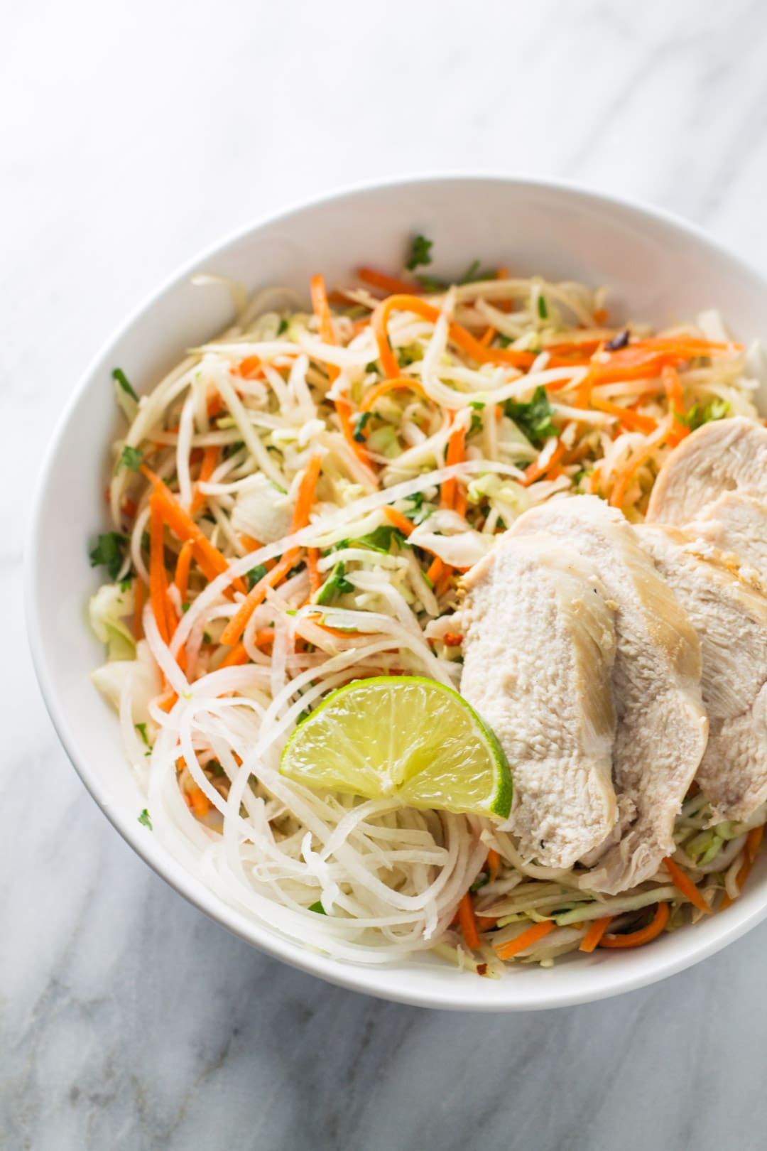 Bowl of low FODMAP Thai citrus salad topped with chicken and a lime wedge