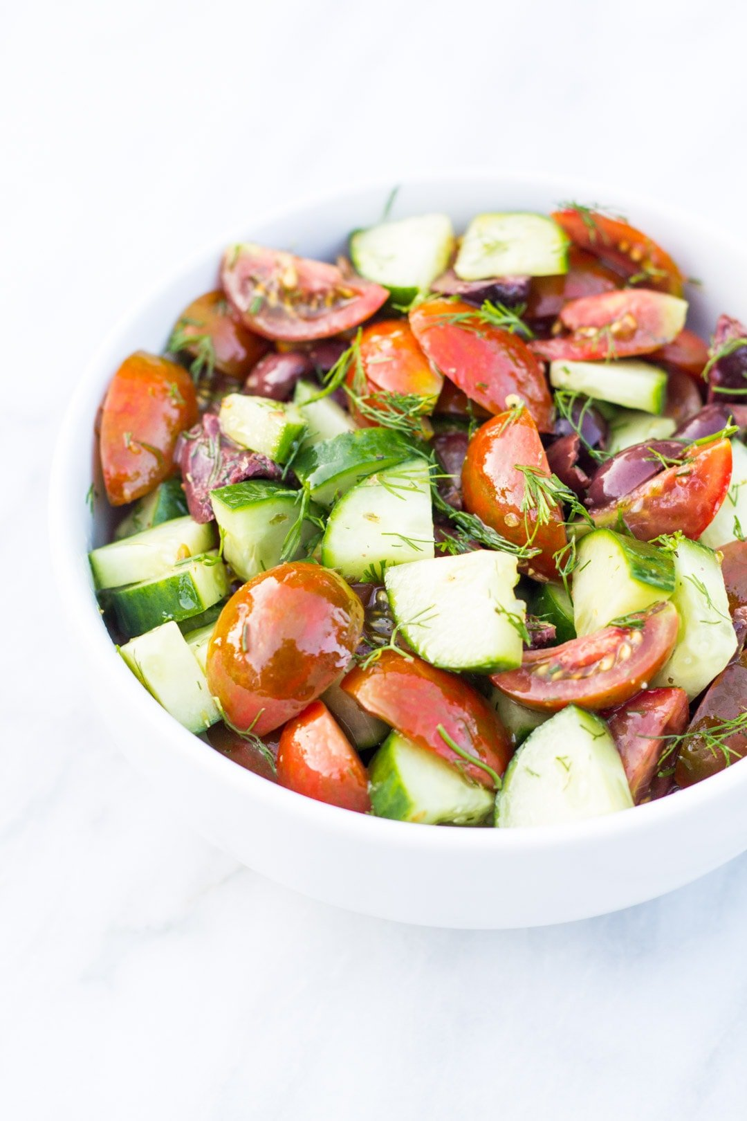 Bowl of quartered cherry tomatoes, quartered cucumber, fresh dill, and a light dressing.