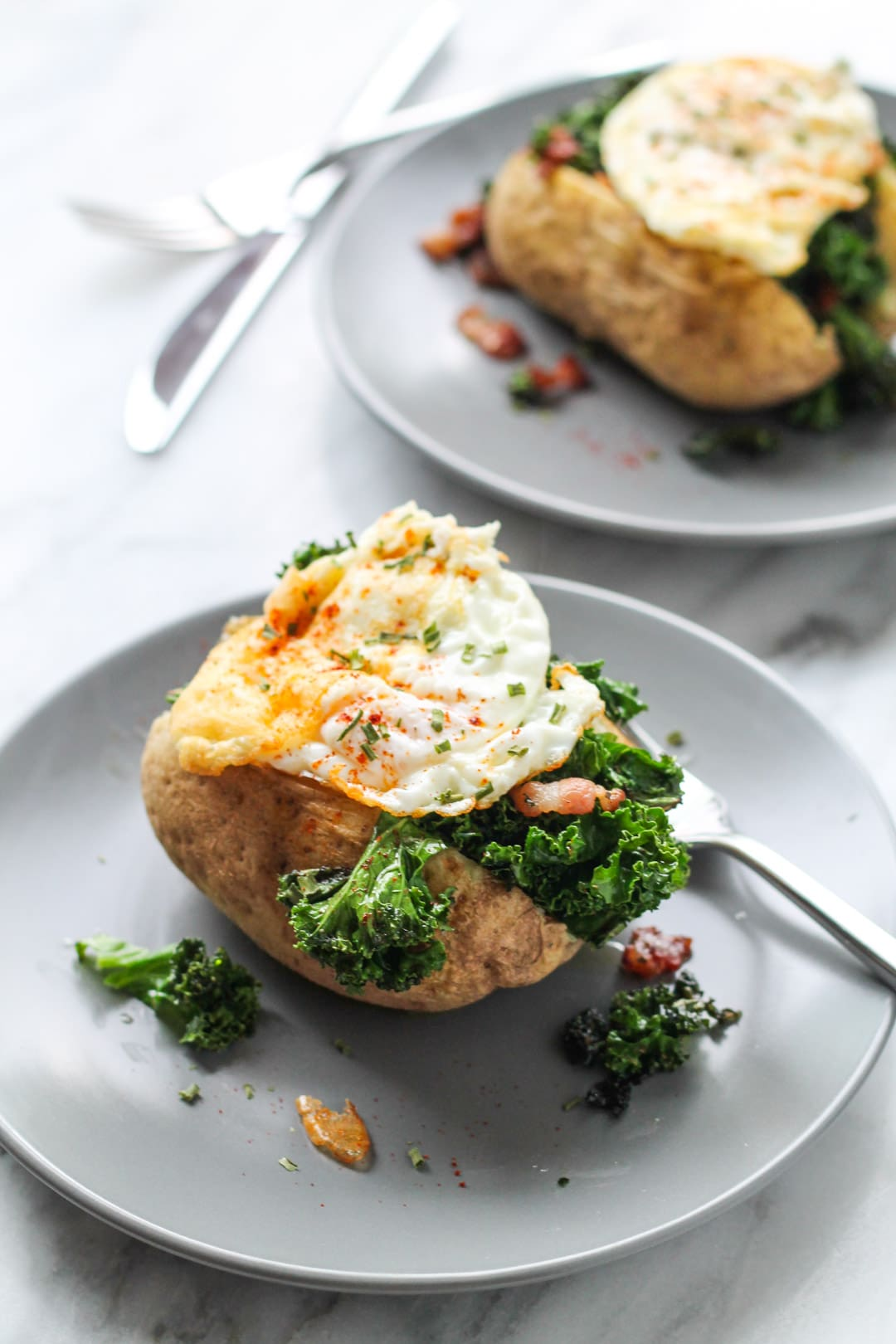 Two plates baked potatoes stuffed with bacon and kale and topped with a fried egg and a sprinkle of chives and paprika.