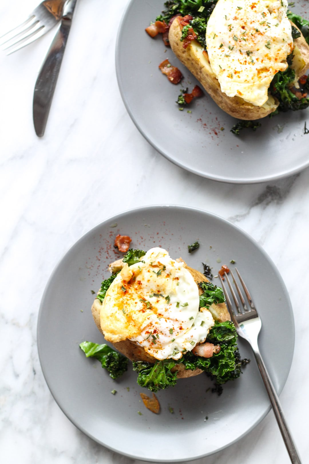 Two plates with a single stuffed potato on each. The potatoes are stuffed with kale and bacon, and topped with a fried egg.