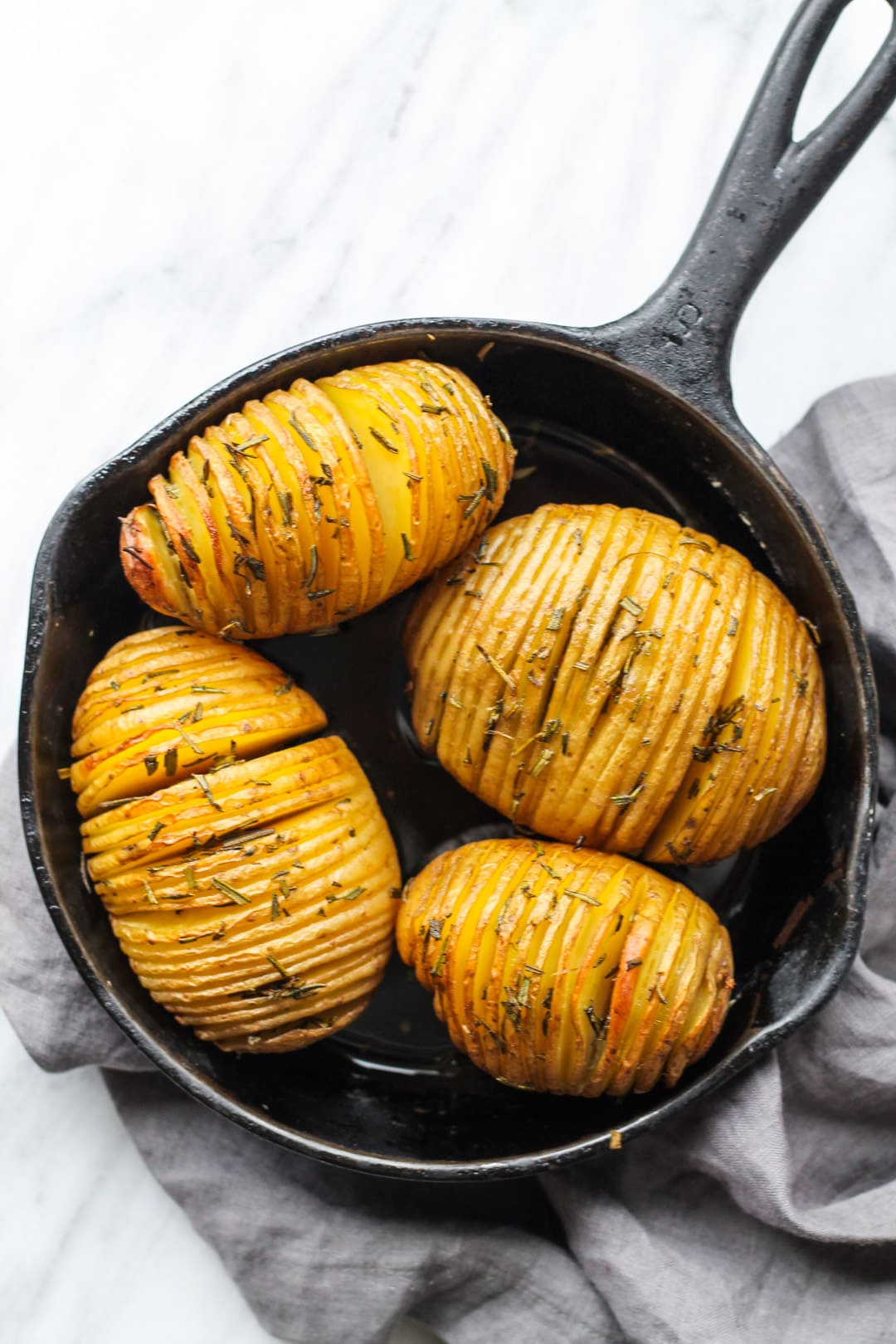 Skillet filled with low FODMAP Hasselback Potatoes with Rosemary